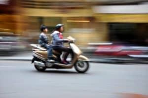 Guldfarvet scooter i fart op bytrafikken