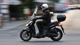 Mand på scooter med beskyttelseshjelm