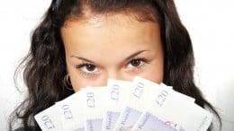Pige med vifte af pengesedler foran ansigtet