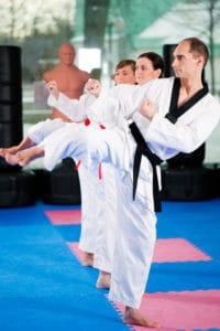 Tre ung mennesker træner spark i kampsport