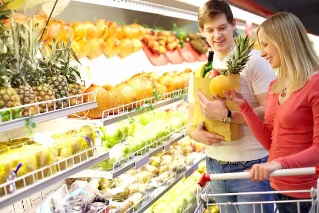 Ungt par køber frugt og grønt i supermarked